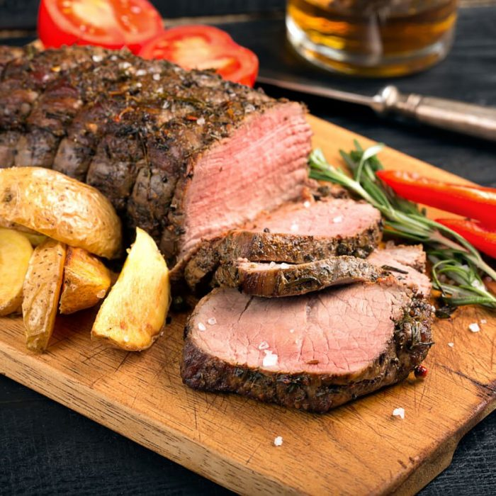 Grilled beef on a cutting board with potatoes and vegetables